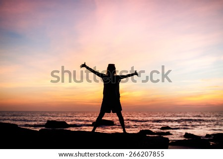Carefree woman dancing in the sunset on the beach. - stock photo