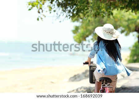 carefree woman having fun enjoying summer riding bicycle at the beach - stock photo