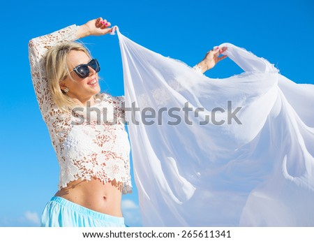 Carefree woman holding white fabric in wind - stock photo