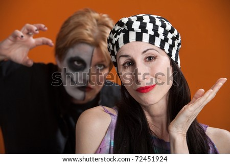 Carefree woman is attacked from behind by another in scary makeup - stock photo