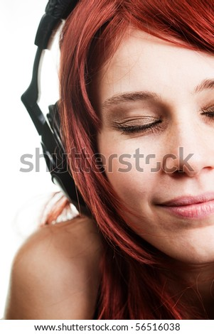 Carefree woman listening music at headphones - stock photo