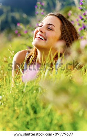 carefree woman sitting in a green field enjoying the summer sunlight - stock photo