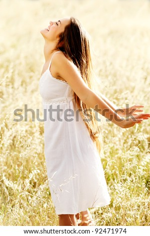 carefree woman stands with her hands out embracing the sunshine at the beach - stock photo