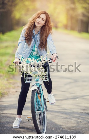 Carefree woman with bicycle riding in park having fun and smiling
