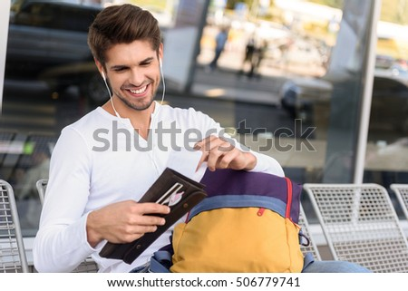 Carefree young man is preparing for trip. He is checking tickets and smiling. Tourist is sitting on bench near airport and wearing earphones