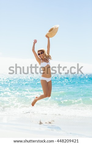 Carefree young woman holding hat and jumping on beach - stock photo