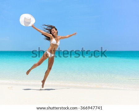 Carefree young woman jumping at beach during summer vacation. Full length of exhilarated female in white bikini. Tourist with arms outstretched is enjoying holidays on sea. - stock photo