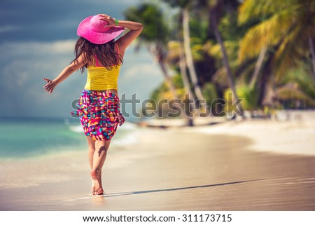 Carefree young woman relaxing on tropical beach - stock photo