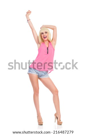 Carefree young woman. Smiling blond fashion girl in high heels and pink top standing with arm raised. Full length studio shot isolated on white. - stock photo