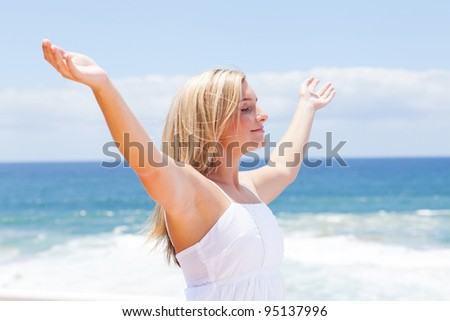 carefree young woman with arms open on beach - stock photo