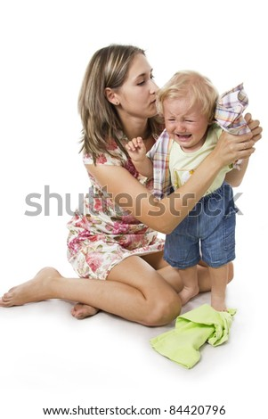 Careful mother dresses the son. Isolated on white. - stock photo
