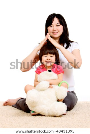 Careful mother holds hands in form of house over her daughter with toy - stock photo