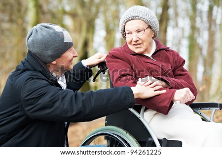 Caregiver careful man walking and embracing disabled senior woman grandmother at wheelchair in nature - stock photo