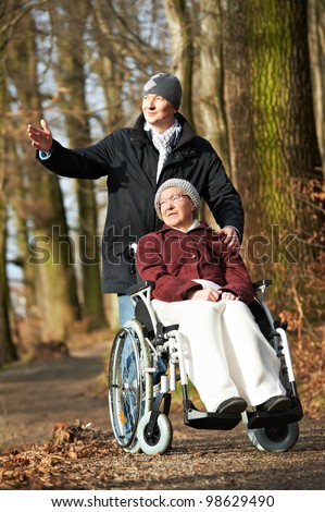 Caregiver careful man walking with disabled senior elderly woman grandmother at wheelchair at park outdoors - stock photo