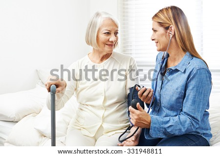 Caregiver doing blood pressure monitoring for senior woman at home - stock photo