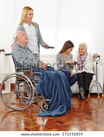 Caregiver entertaining senior citizens in a retirement home - stock photo