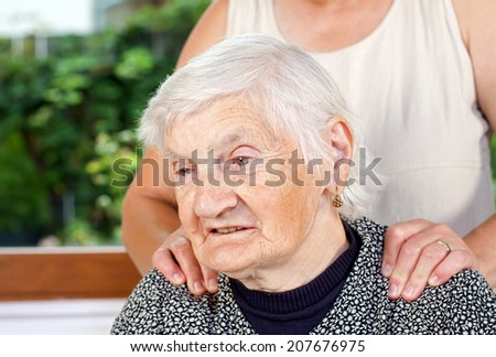 Caregiver giving a massage to an elderly patient - stock photo