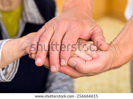 Caregiver giving helping hands for elderly woman - stock photo