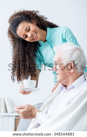 Caregiver giving senior man cup of coffee - stock photo