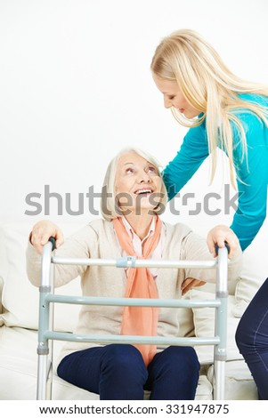 Caregiver helping old woman with walker getting up from sofa at home - stock photo