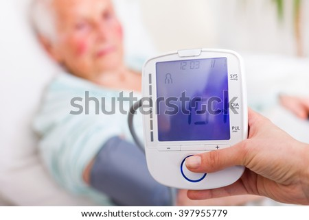 Caregiver measuring elderly woman's systolic blood pressure in hospital. - stock photo