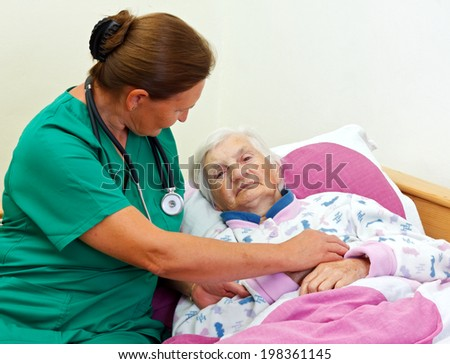 Caregiver with an elderly patient at home - stock photo