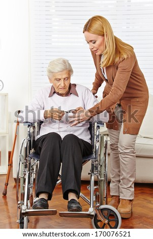 Caregiver woman giving glasses to disabled senior citizen in wheelchair - stock photo