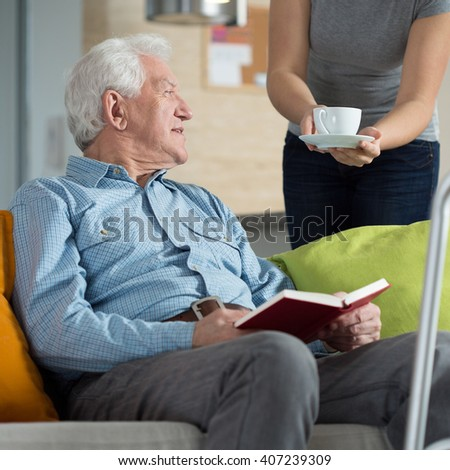 Carer giving disabled man cup of coffee - stock photo