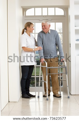Carer Helping Elderly Senior Man Using Walking Frame - stock photo