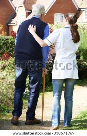 Carer Helping Senior Man To Walk In Garden Using Walking Stick - stock photo