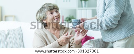 Carer is giving cup of tea to elderly woman  - stock photo