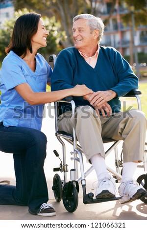 Carer Pushing Senior Man In Wheelchair - stock photo