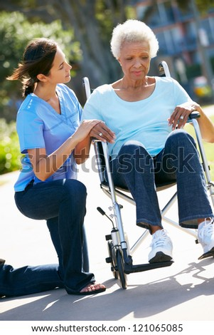 Carer Pushing Unhappy Senior Woman In Wheelchair - stock photo