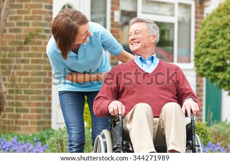 Carer With Senior Man In Wheelchair - stock photo