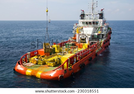 Cargo being loaded from a offshore platform onto a supply vessel - stock photo
