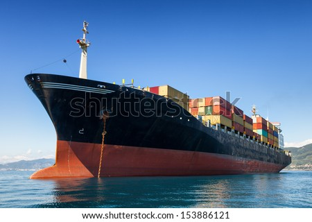 cargo container ship anchored in harbor - stock photo