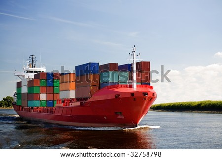 cargo container ship - freighter navigating river - stock photo