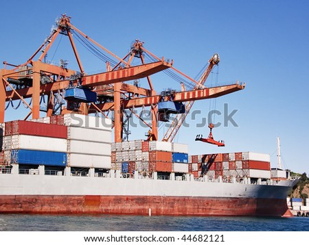 Cargo container ship under cranes in sea port - stock photo