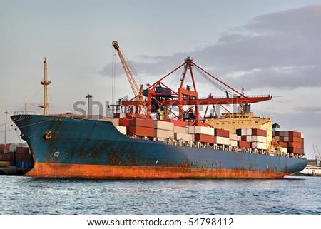 Cargo container ship under cranes in the sea port - stock photo