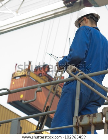 Cargo container worker - watching the loading plan . Real situation photo. - stock photo