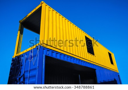 Cargo containers blue and yellow on blue sky background.