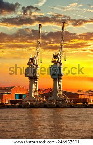 Cargo cranes at sunset in port of Gdansk, Poland.  - stock photo
