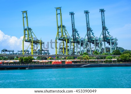 Cargo cranes in jetty by the water over blue sky - stock photo