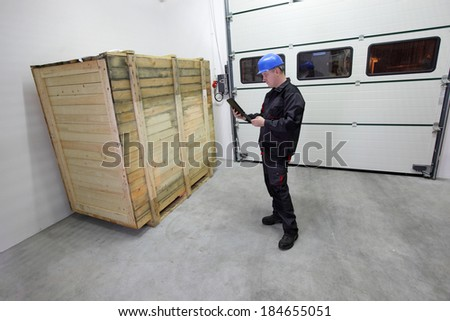 cargo - delivery, industrial worker in hardhat and uniform checking large wooden box on tablet in warehouse