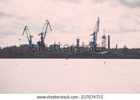 cargo dock and cargo ships in seaport in Riga. latvia - retro, vintage style look - stock photo