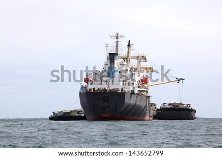 cargo liner freight Ship with containers and tug ship - stock photo