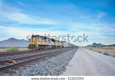 Cargo locomotive railroad engine crossing Arizona desert wilderness during early evening.