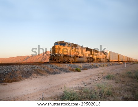 Cargo locomotive railroad engine crossing Arizona desert wilderness during sunset - stock photo