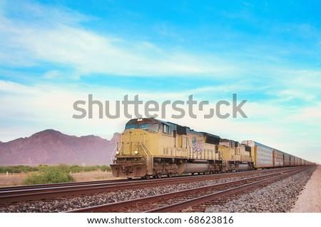 Cargo locomotive railroad engine crossing Arizona desert wilderness during sunset - stock photo