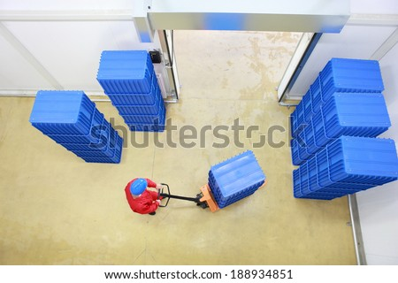 cargo - overhead view of worker in red uniform loading blue containers to storehouse